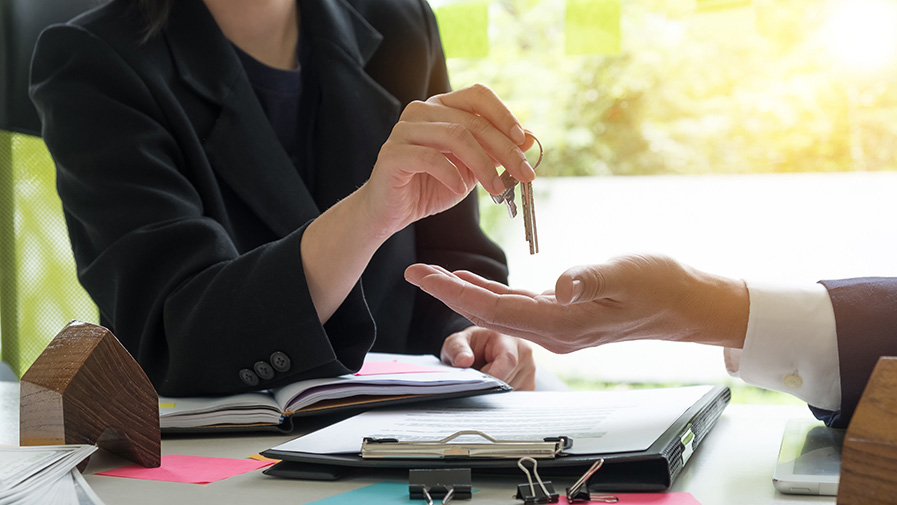 estate agent giving house keys to man and sign agreement with house model, calculator agreement in office
