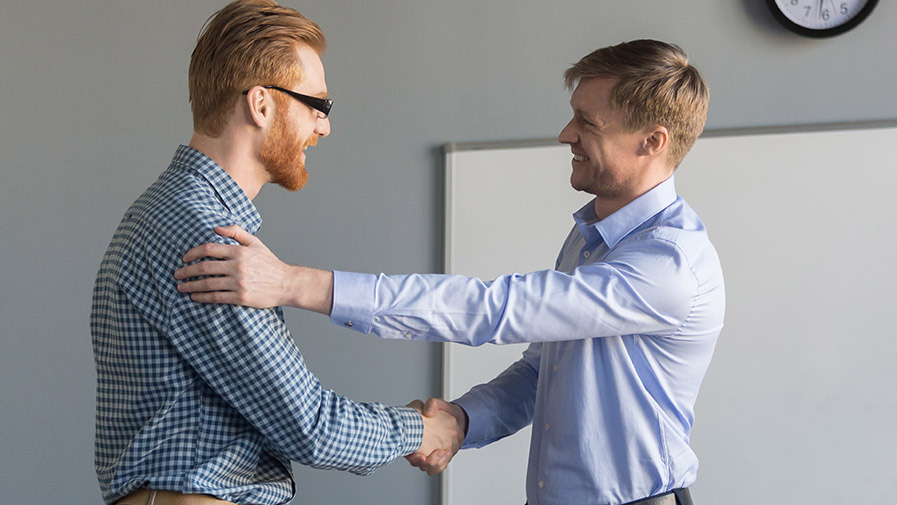 Happy ceo handshaking successful employee supporting congratulat