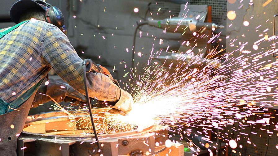 Mann mit Trennschleifer bearbeitet Werkstück