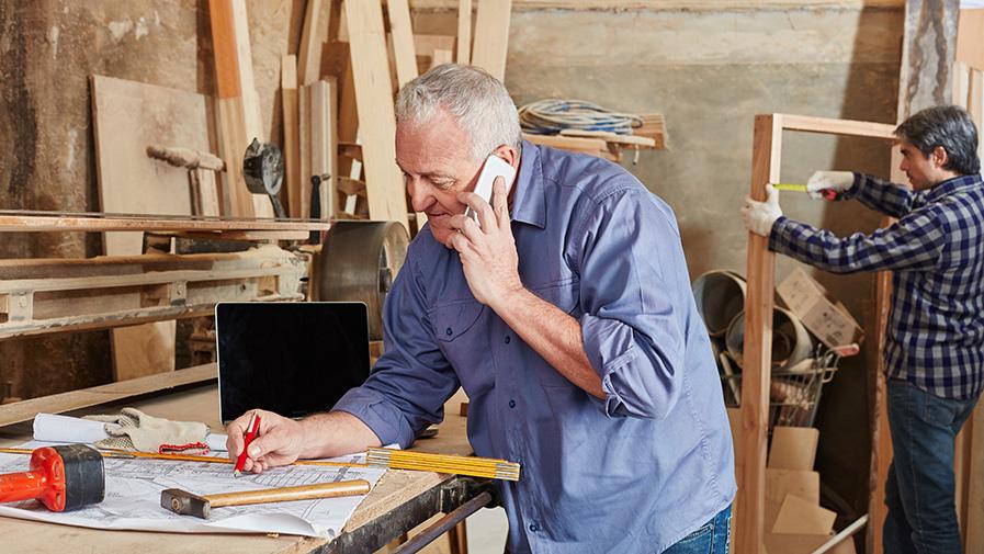 Senior als Chef telefoniert mit Mobiltelefon