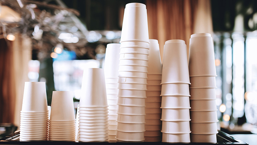Lovely coffee glasses are standing on the top of the coffee machine in a cozy coffee shop.