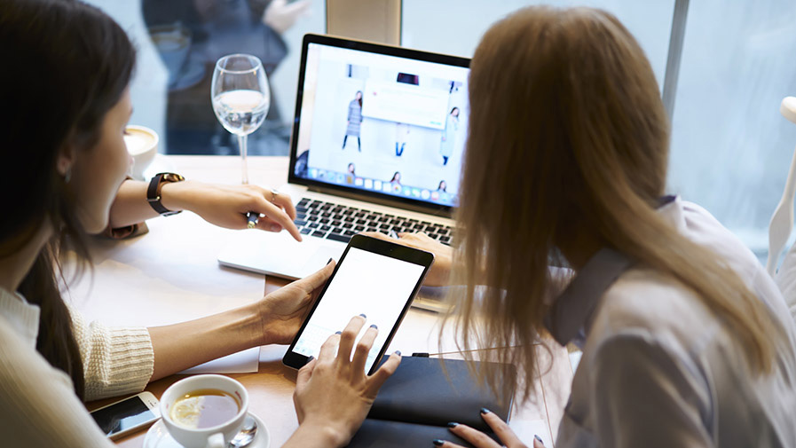 Creative female IT developers coding web site collaborating while working on design layout choosing right colors and multimedia on informal meeting in friendly atmosphere in coffee shop using devices