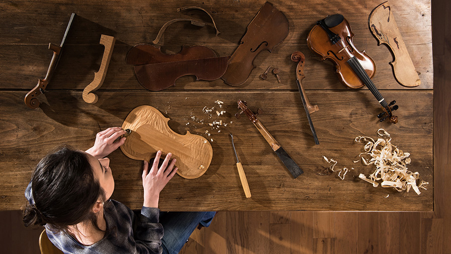 Top view. female luthier working on the creation of a violin