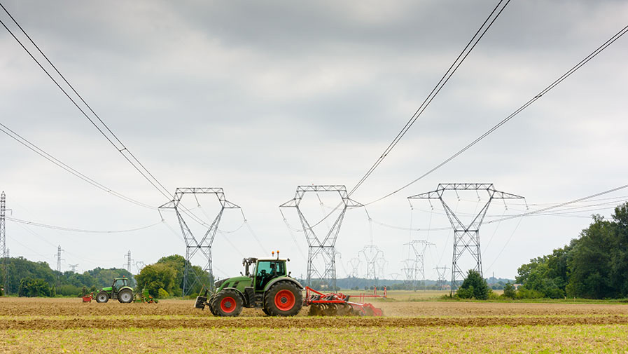 Dozens of transmission towers and high-voltage lines with tractors ploughing a field in the foreground, under a heavy sky.