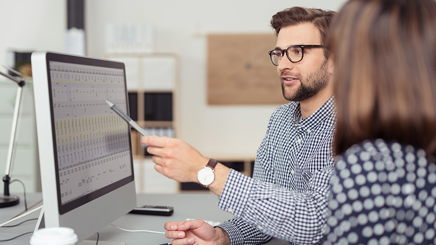 geschäftsmann erklärt seiner kollegin etwas am computer
