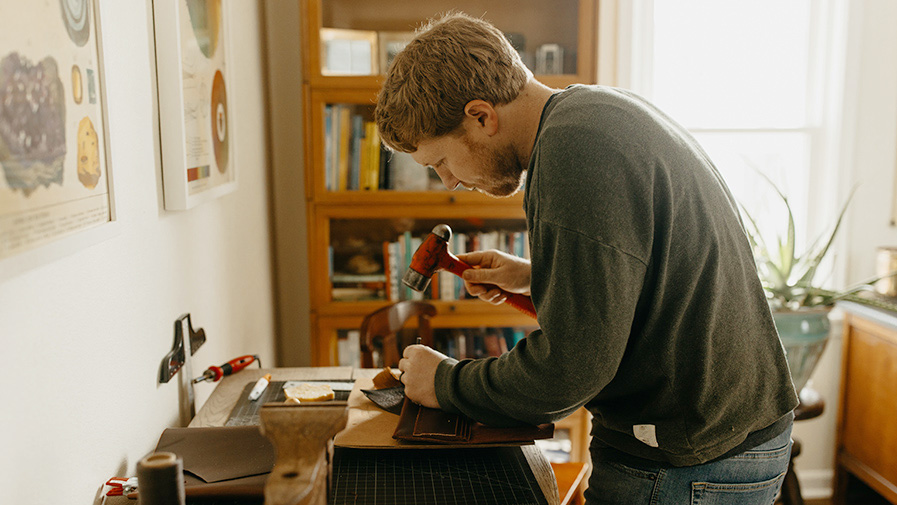 Man Hand Making a Leather Wallet Hammering Stitch Holes in Indoor Studio