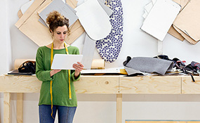 Portrait of a fashion designer with tablet in her studio