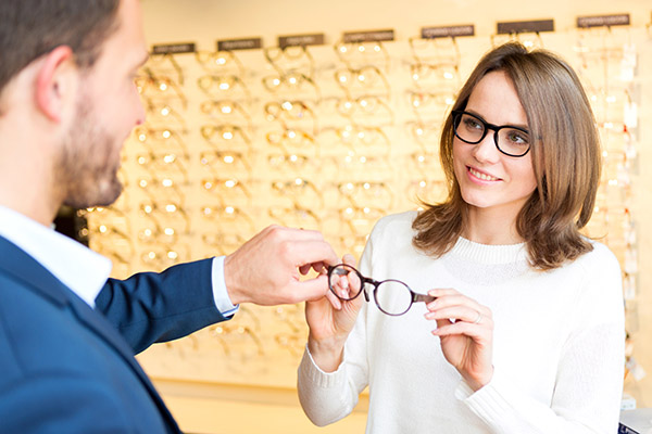 Young attractive  woman testing new glasses with optician