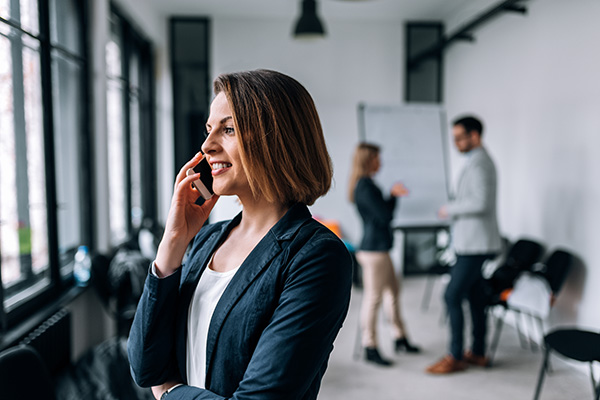 Young businesswoman talking on mobile phone with colleagues in background.